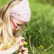 Girl picking yellow spring flower — Stock Photo