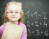 Portrait of smart schoolchild standing at blackboard — Stock Photo