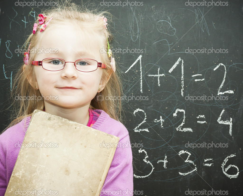 Portrait of smart schoolchild standing at blackboard and  holding a old sheet — Stock Photo #9118057
