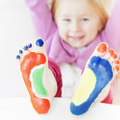 Little girl with feet painted — Stock Photo