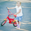 Little blond girl with red bike — Stock Photo