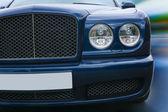 Prestigious dark blue car goes on road — Stock Photo