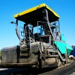 Stock Photo: Asphalt spreader on new road to city.