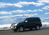 SUV goes on winter road — Stock Photo