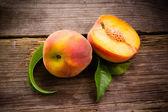 Fresh organic fruit - peaches on wood background — Stock Photo