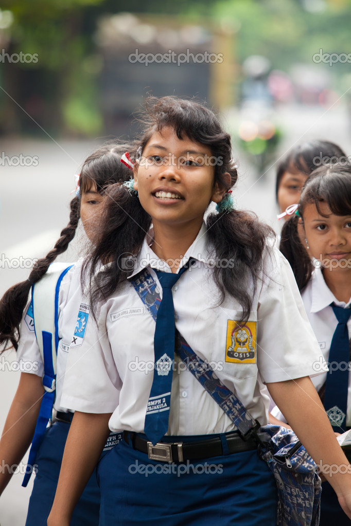 BALI - JANUARY 24. Balinese school kids in uniform walking home on street in Bali on January 24, 2012 in Bali, Indonesia. Uniforms are worn in Bali as to not distinguish class, religion and social status.  Stock Photo #9314996