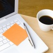 Pen with postit note, laptop and cup of coffee — Stock Photo