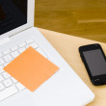 Blank postit note on white laptop keyboard — Stock Photo