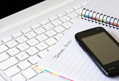 Cell phone with laptop and spiral notebook — Stock Photo
