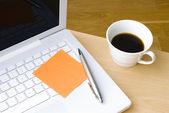 Pen met postit opmerking, laptop en kopje koffie — Stockfoto