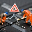 Miniature figures working on a computer keyboard. - Stock Photo