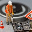 Miniature figures working on a DVD drive. - Stock Photo