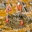 Stock Photo: Miniature figures working on circuit board.