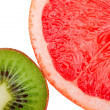 Macro shot of a red grapefruit and a kiwi isolated on white - Stock Photo