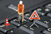 Miniature figures working on a computer keyboard. — Stock Photo