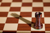 Chess piece - a black rook on a chessboard. — Stock Photo