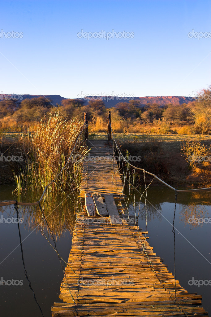 Rope bridge leading across a river to a small island. — Stock Photo #9073973