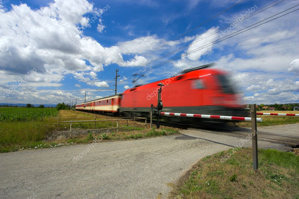 Train passing through a railway crossing against a blue sky with an interesting cloudscape. Motion blur is used to show the movement of the train. — Stock Photo #9074029