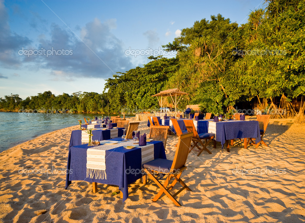 Dinner on the beach - several tables are laid out for dinner on an tropical beach. — Stock Photo #9074646