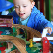 Little boy playing with his wooden train set - Stock Photo