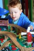 Little boy playing with his wooden train set — Stock Photo