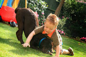 Little boy playing with his cute chocolate labrador puppy — Stock Photo