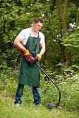Ogrodnik z przycinarka do trawnika — Zdjęcie stockowe