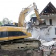 Stock Photo: Digger demolishing house