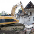 Digger demolishing house - Stock Photo