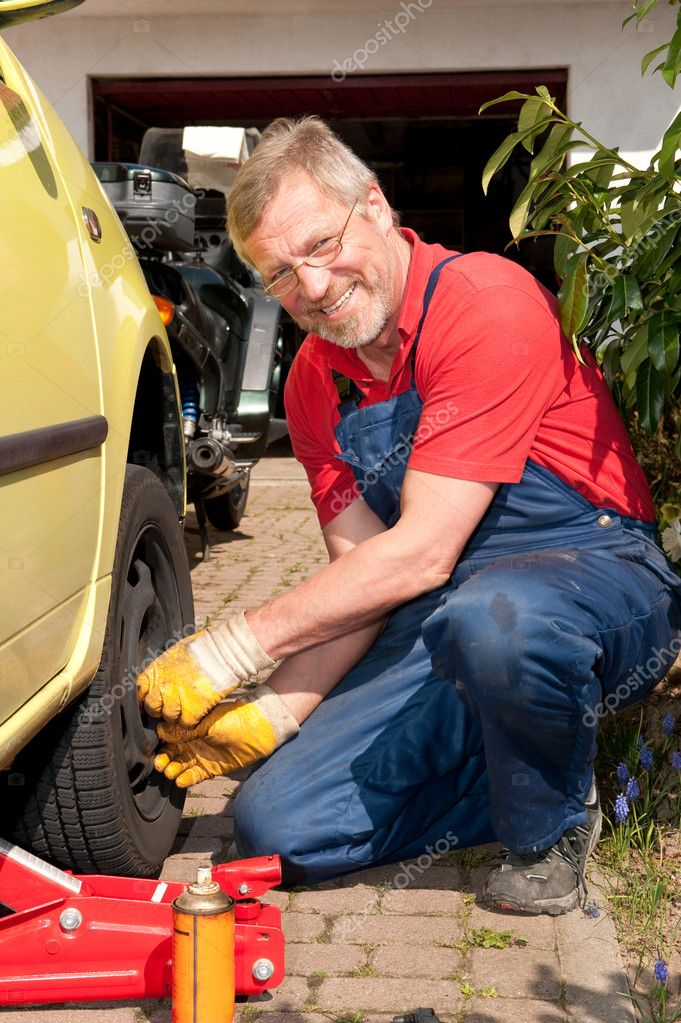 Smiling mechanic is checking the tire pressure — Stock Photo #9496306