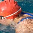 Athletic swimmer in action in a swimming pool - Stock Photo