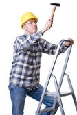 Craftsman on a ladder with a hammer — Stock Photo