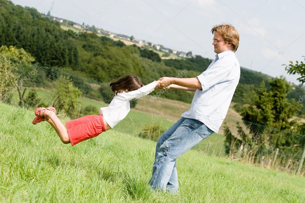 Young father is playing with his daughter in a famer's field — Stock Photo #9713436