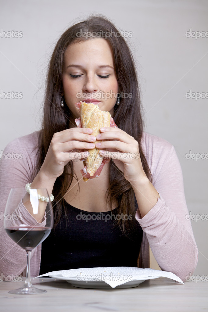 Young woman at the table with a sandwich and a glass wine — Stock Photo #10475169