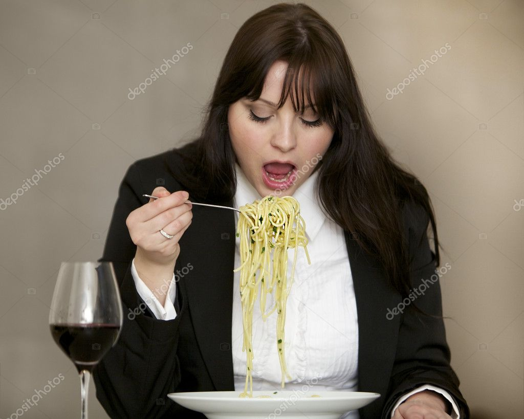 Very hungry woman with a large portion of pasta on her fork. A glass of red wine is on the table. — Stock Photo #10628008
