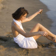 Young woman sitting on sand - Stock Photo
