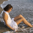 Young woman sitting on sand - Stockfoto