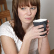 Young woman with tea - Stock Photo