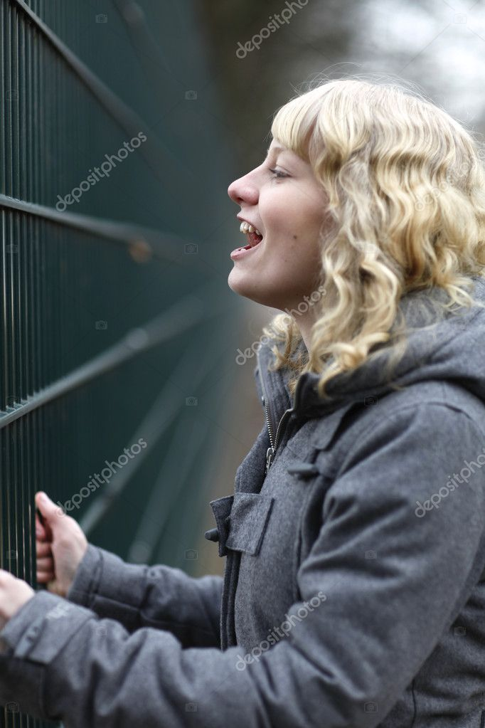 Girl screaming and looking through green metal fence — Stock Photo #9224287