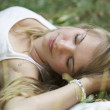 Beautiful young woman sleeping on grass - Stock Photo