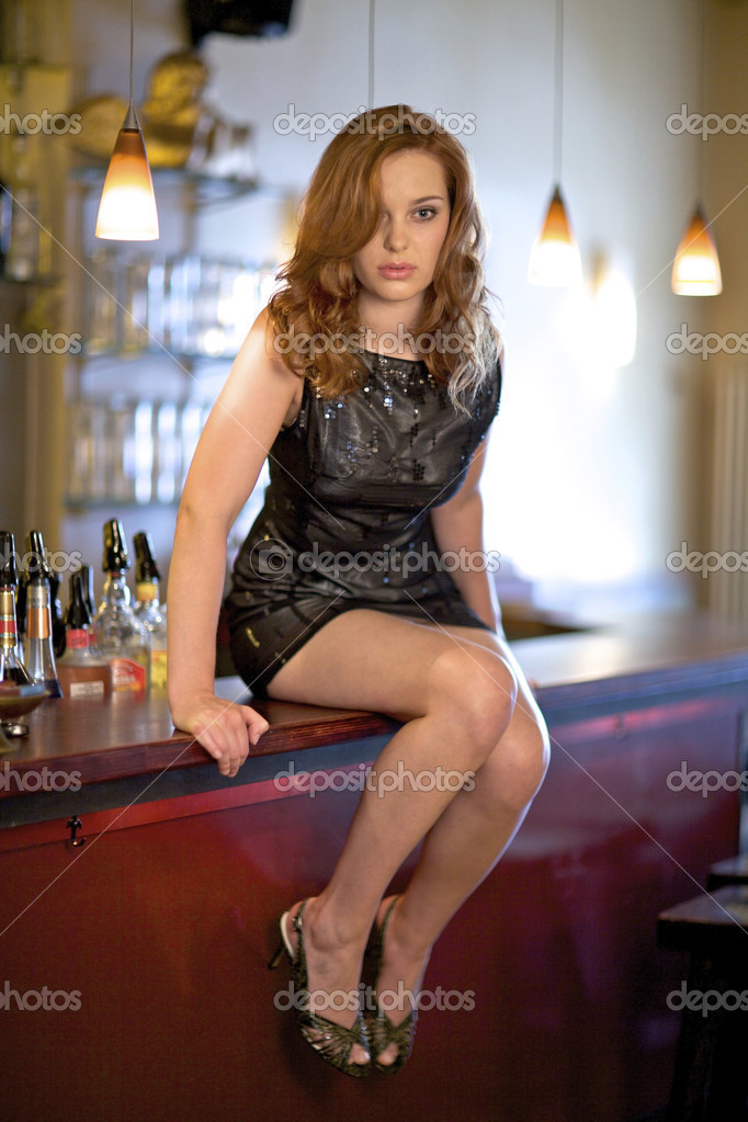 Attractive young woman sitting on the bar counter  Stock Photo #9739944