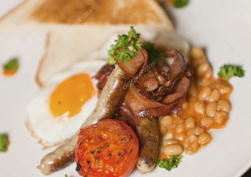 Delicious English breakfast plate with bacon, beans, eggs, sausages, toast, and tomatoes.  Stock Photo #9764967