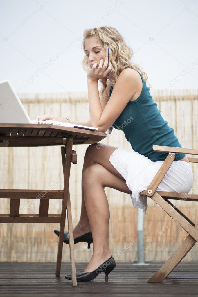 Concentrated girl sitting outdoors with book and computer. — Stock Photo #9767903