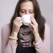 Young woman drinking tea or coffee - Stock Photo