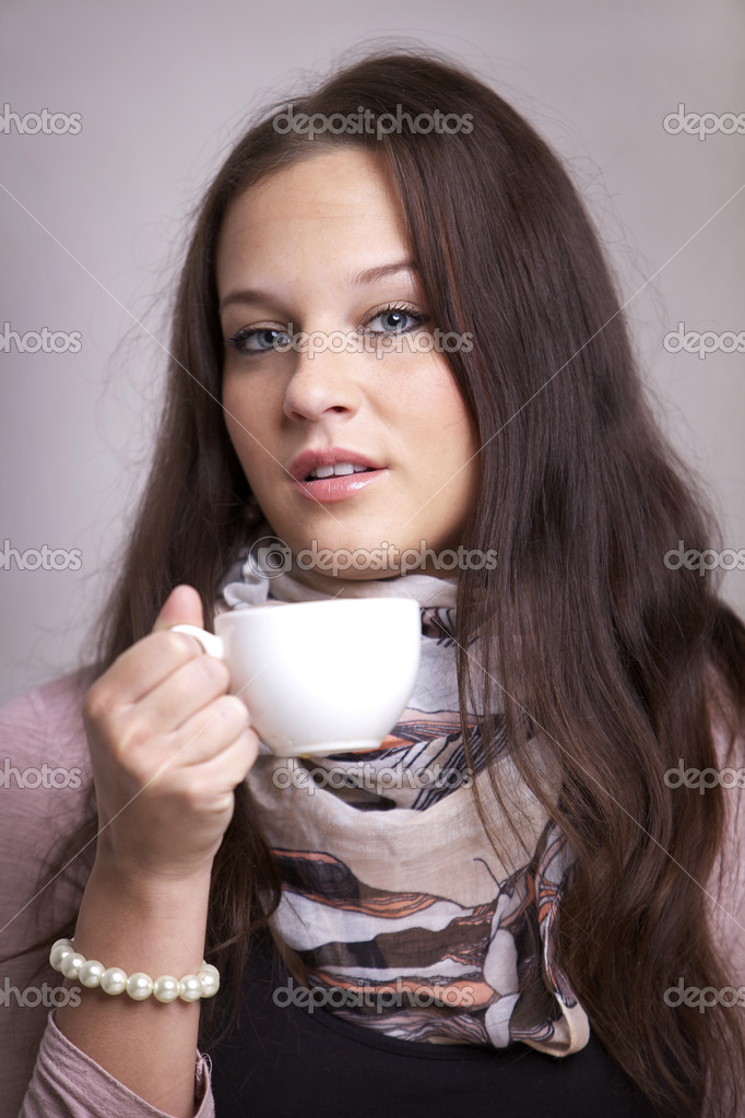 Attractive young woman sitting at the table holding a cup of coffee or tea — Stock Photo #9799031