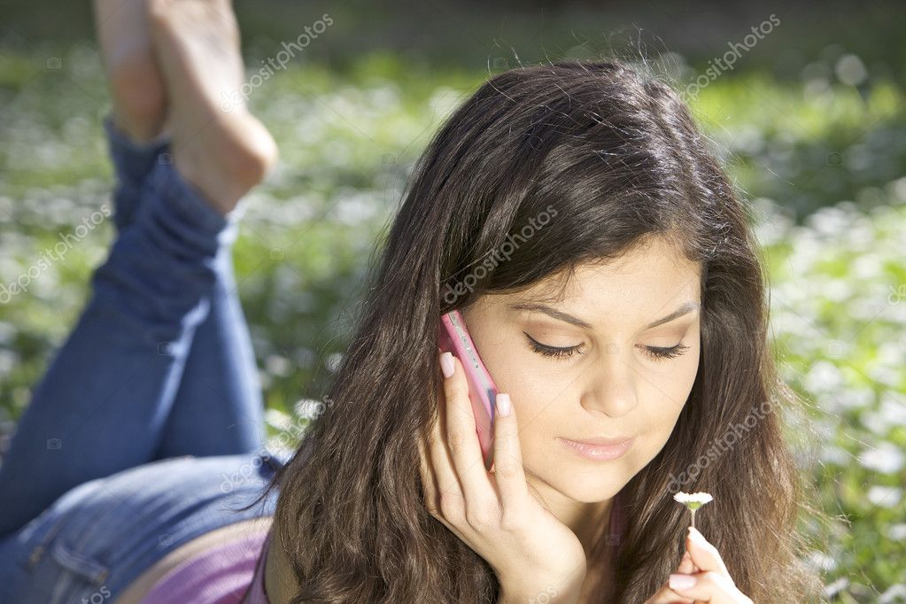 Beautiful young woman laying on the grass in park with flowers and telephone — Foto Stock #9805980