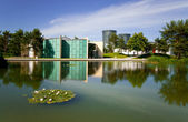 Modern apartments in the green park with lake — Stock Photo