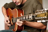 Playing a 12 string acoustic guitar — Stock Photo