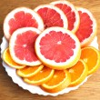Royalty-Free Stock Photo: Rings of grapefruit and orange on a white plate