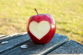 Lonely apple with carved heart — Stock Photo